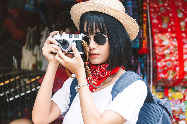 Young woman photographing with camera in city