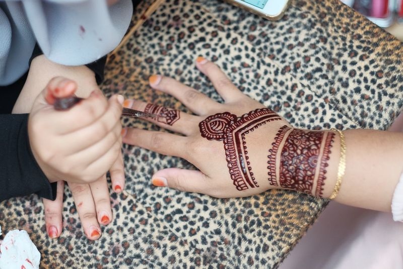 Cropped Image Of Beautician Applying Henna Tattoo On Woman Hand