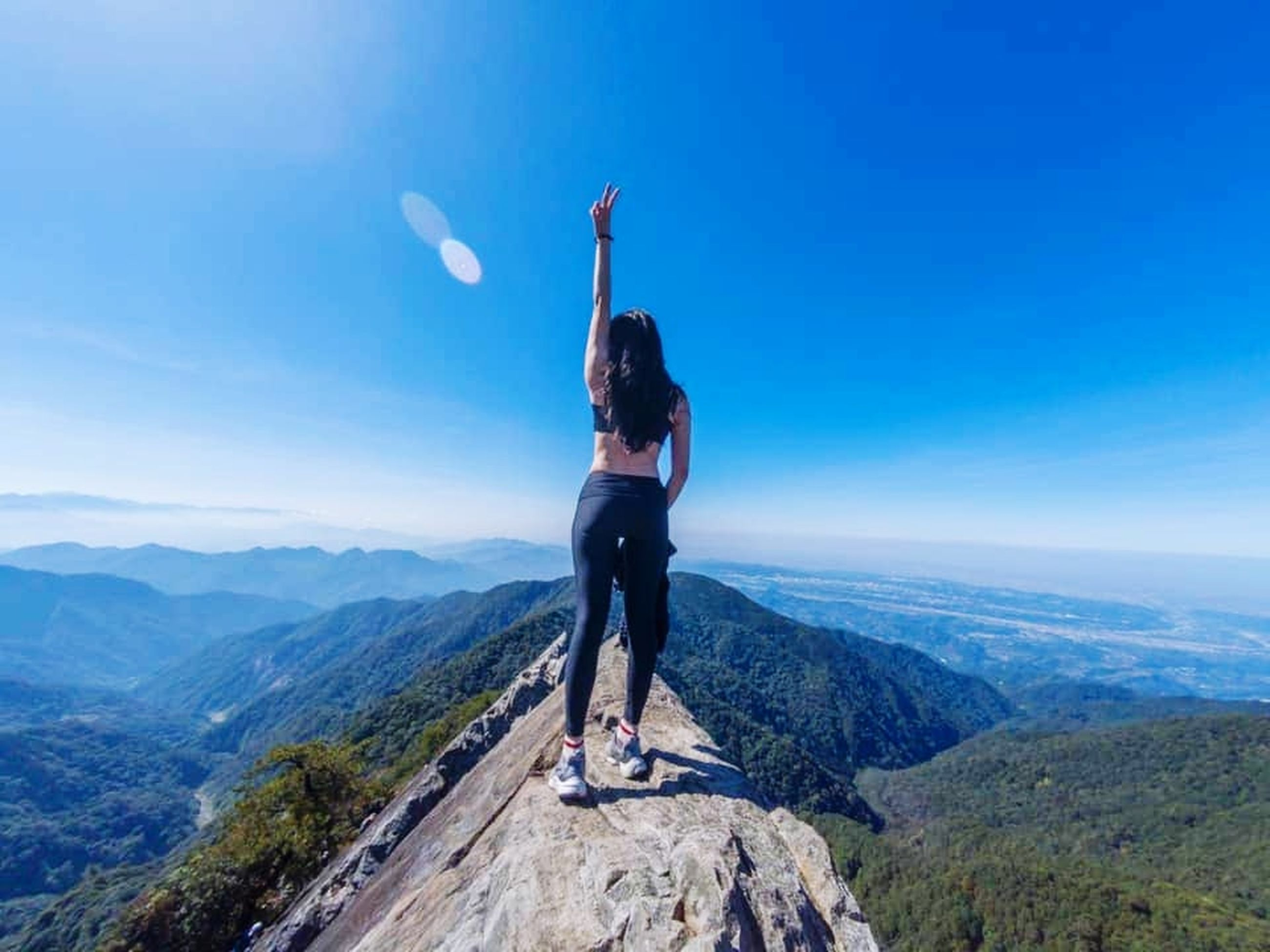 mountain, one person, sky, scenics - nature, adult, leisure activity, nature, beauty in nature, adventure, environment, landscape, mountain range, full length, sports, activity, tranquility, lifestyles, tranquil scene, arm, extreme sports, blue, women, mountaineering, young adult, hiking, vacation, day, travel, limb, trip, rock, holiday, standing, vitality, exercising, outdoors, mountain peak, achievement, non-urban scene, travel destinations, ridge, success, determination, summit, challenge, idyllic, looking at view, human limb, arms raised, copy space, land, cloud, remote, sunlight, solitude, hand, rear view, motivation, climbing, courage, clear sky, recreation, casual clothing, strength, aspirations, exploration, balance