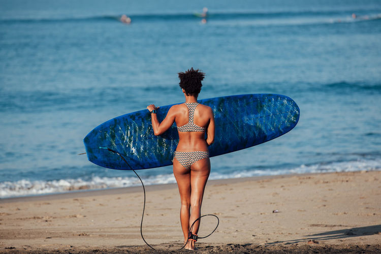 Rear View Full Length Of Woman With Surfboard Walking At Beach