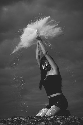 Young woman splashing powder against sky
