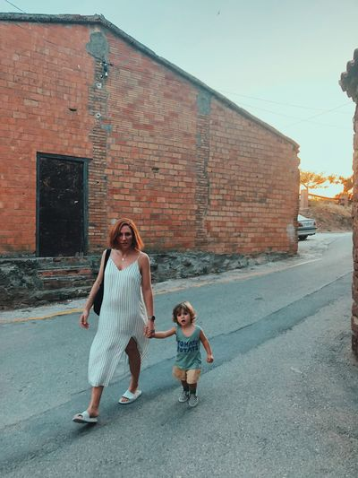 Full length of mother and daughter standing on brick wall