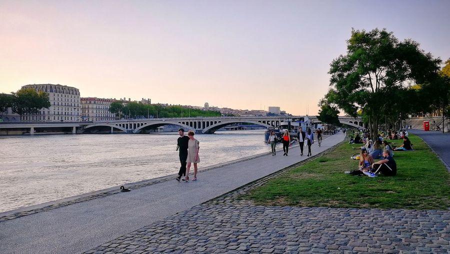 People walking on bridge over river against sky in city