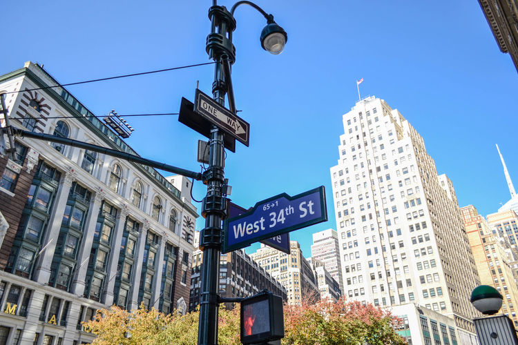 Low Angle View Of Street Name Sign And Buildings Against Blue Sky