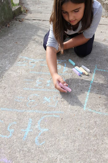 High angle of girl writing with chalk on footpath