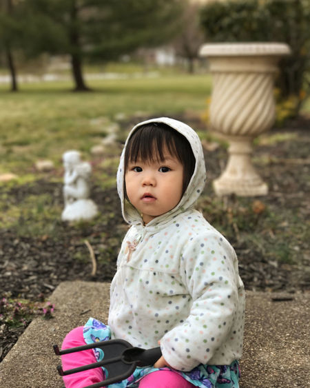 Portrait of cute girl sitting outdoors
