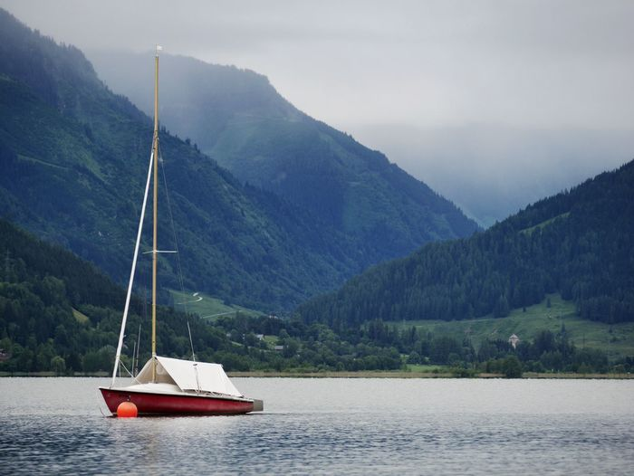 Sailboat in lake against mountains