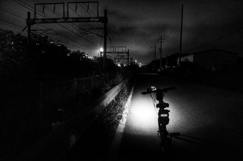 Vehicles on illuminated road against sky at night