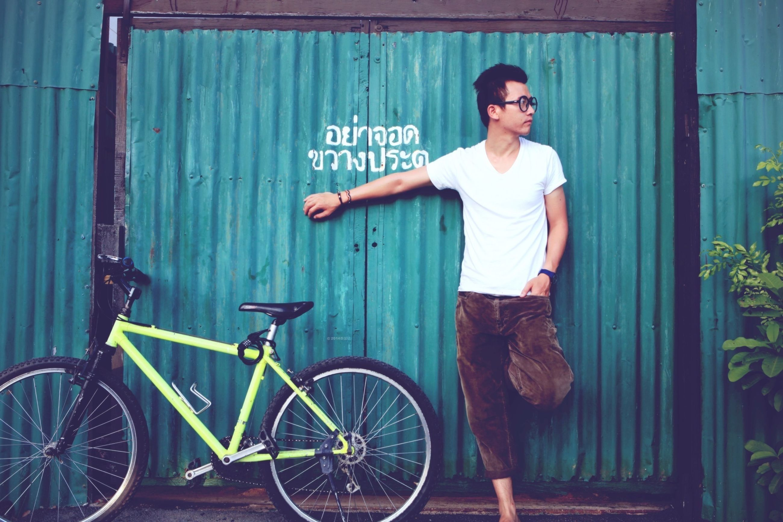 bicycle, person, casual clothing, young adult, full length, lifestyles, front view, mode of transport, transportation, looking at camera, land vehicle, leisure activity, portrait, smiling, leaning, standing, building exterior, built structure
