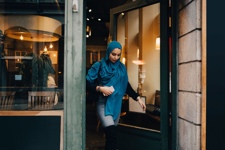 Young woman wearing hijab leaving store in city