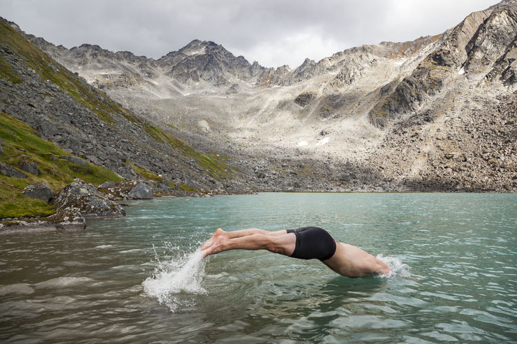 Man surfing in lake against mountain