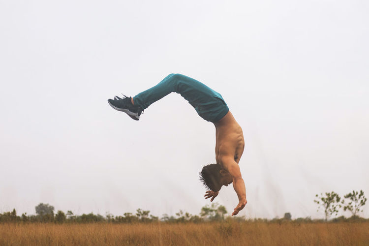 Teenage boy jumping upside down on land against clear sky