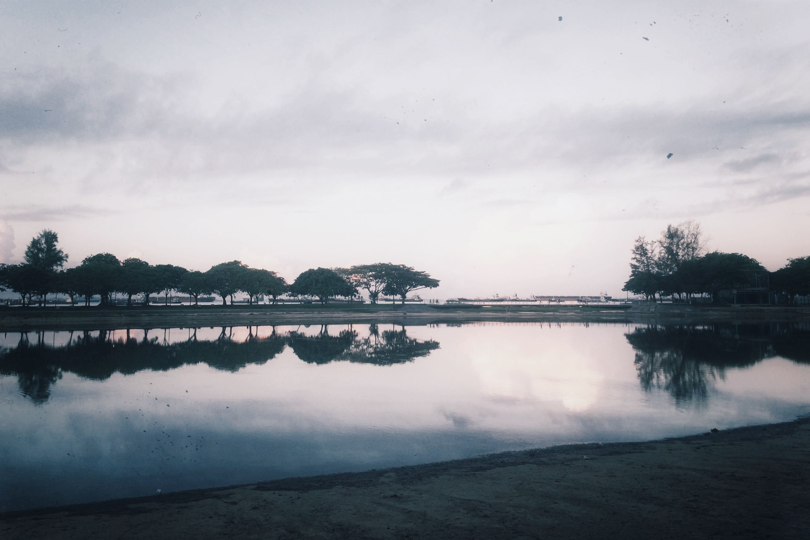 water, tranquil scene, sky, tranquility, scenics, reflection, lake, tree, beauty in nature, cloud - sky, nature, calm, cloud, idyllic, standing water, cloudy, waterfront, beach, non-urban scene, outdoors