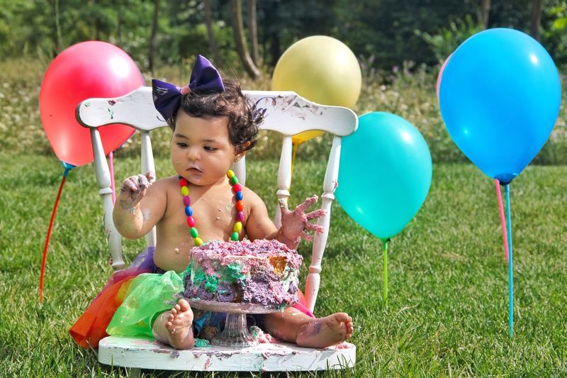 Cute Baby Girl Sitting On Chair Outdoors During Birthday Party