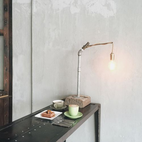 Breakfast on table by illuminated light bulb against wall
