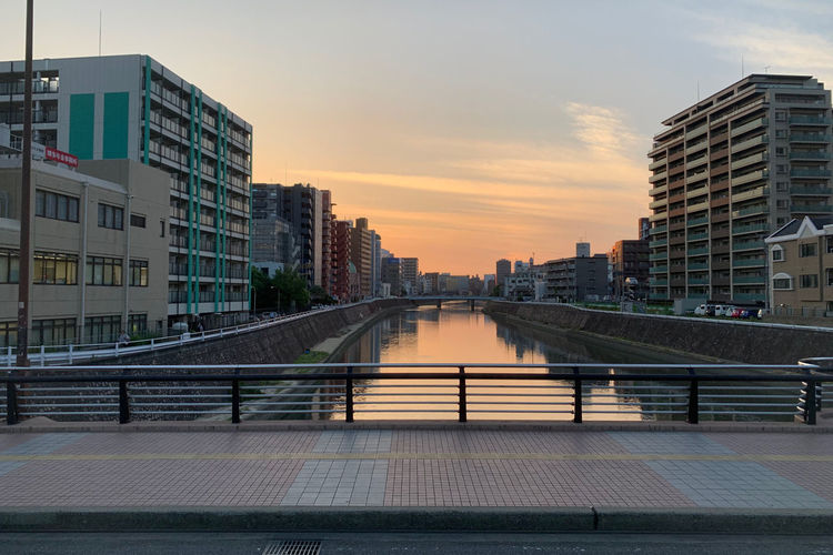 Bridge over canal amidst buildings in city during sunset