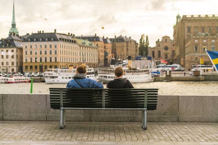 Rear view of people sitting on bench against buildings in city