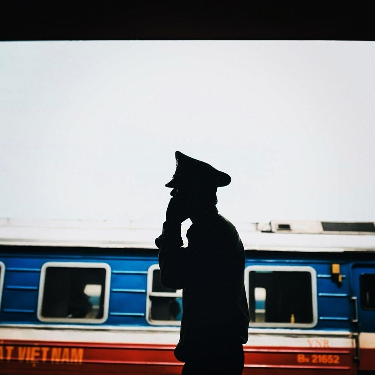 Silhouette transport conductor using phone with train in background