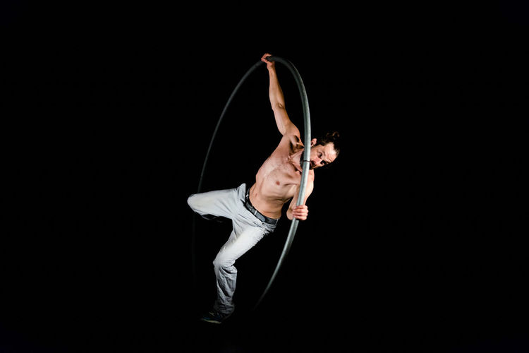 Circus Adult Balance Black Background Copy Space Effort Exercising Expertise Flexibility Full Length Healthy Lifestyle Holding Indoors  One Person Skill  Sport Strength Studio Shot Vitality Young Adult