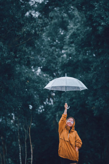 Girl holding umbrella standing in forest