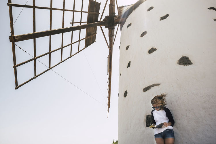 nice beautiful cheerful lady with blonde curly hair standing under a windmill in outdoor scenic place reading a book and enjoying the leisure activity. happy lifestyle concept for people smile Real People Lifestyles Leisure Activity One Person Rear View Casual Clothing Men Climbing Low Angle View Nature Day Outdoors Architecture Built Structure Full Length Sky Wall - Building Feature Three Quarter Length White Color Caucasian Standing Shorts Vacations Windmill Curly Hair