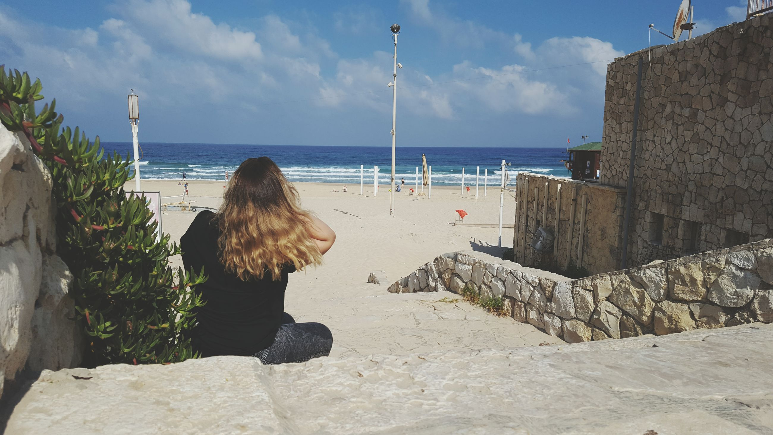 sea, rear view, real people, one person, water, sky, cloud - sky, architecture, horizon over water, built structure, retaining wall, women, building exterior, day, leisure activity, nature, rock - object, outdoors, lifestyles, full length, beach, sitting, beauty in nature, standing, scenics, people