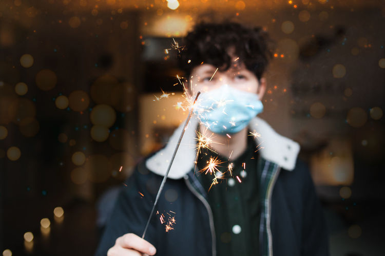 Portrait of woman wearing mask holding sparkler