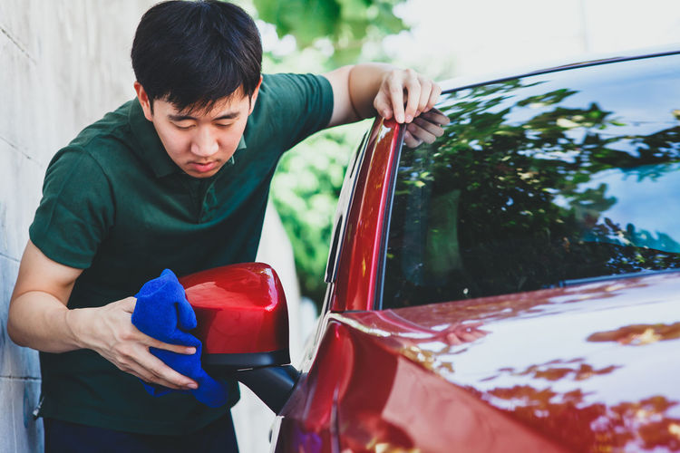 Young man washing and wiping a car in the outdoor Asian  Automobile Car Wash Cleaner Cleaning Mechanic Service Washing Automotive Car Clean Day Dirty Garage Human Hand One Person Outdoors Polish Polishing Real People Transportation Vehicle Wash Wax Waxing