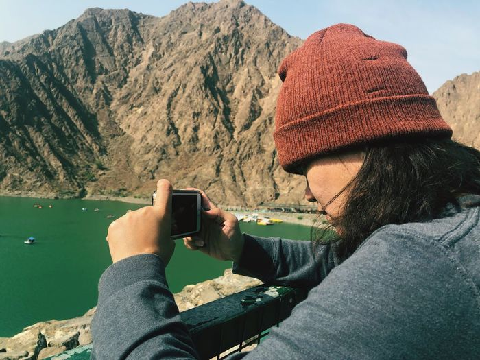 Side view of woman photographing with mobile phone against mountains