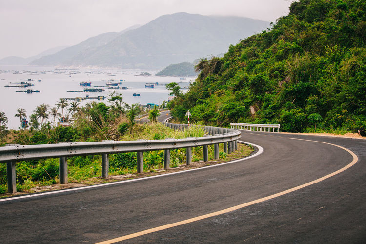 Road by sea against mountains in city