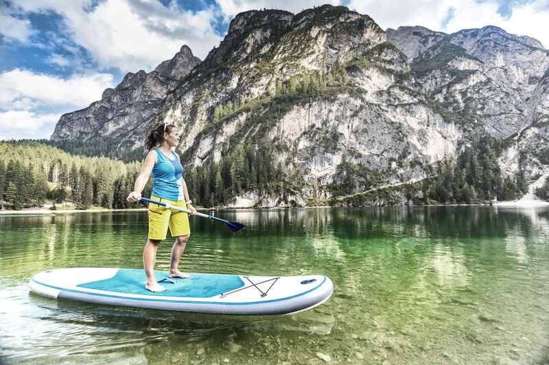 Woman paddleboarding in lake against dolomites mountain
