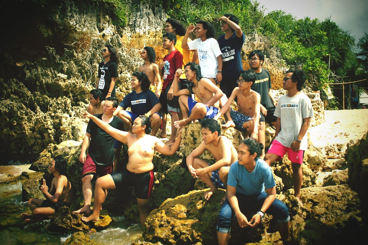 real people, rock - object, outdoors, large group of people, day, fun, standing, men, water, togetherness, tree, sitting, full length, nature, people