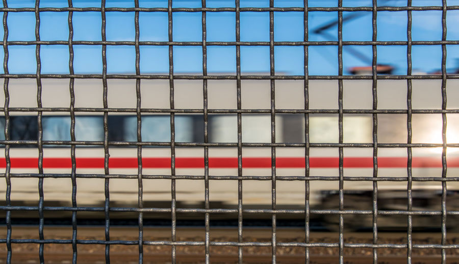 Full frame shot of chainlink fence against train