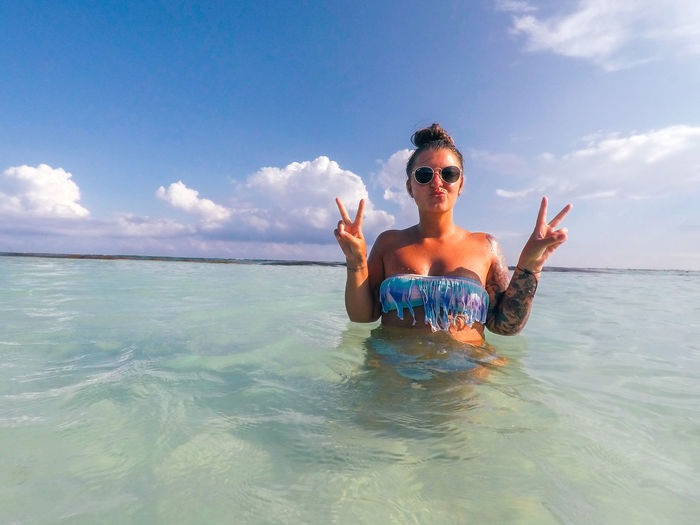 Portrait of smiling young woman gesturing in sea against blue sky