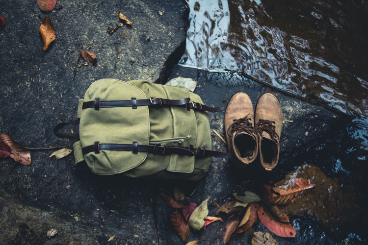 High angle view of shoes and backpack at lake
