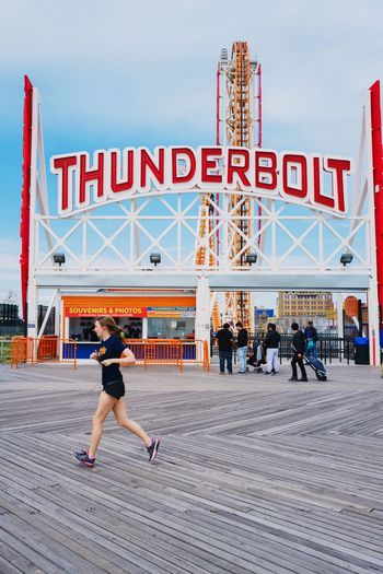 Full Length Text Leisure Activity Communication Person Lifestyles Walking Culture City Sky Bridge - Man Made Structure In Front Of Outdoors Day Cloud Red Footpath City Life Tourism International Landmark Coney Island