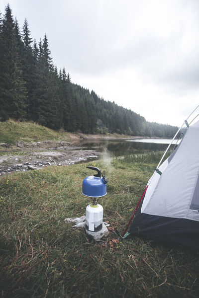 Camping life. Gas fuel canister and a whistling kettle Camping Gas Beauty In Nature Camping Cloud - Sky Day Environment Field Grass Growth Land Landscape Mountain Nature No People Outdoors Plant Primus Scenics - Nature Sky Tent Tentacle Tranquil Scene Tranquility Tree