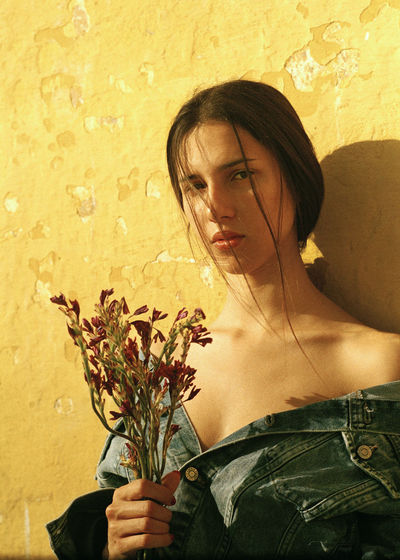 Portrait of young woman holding flower against wall