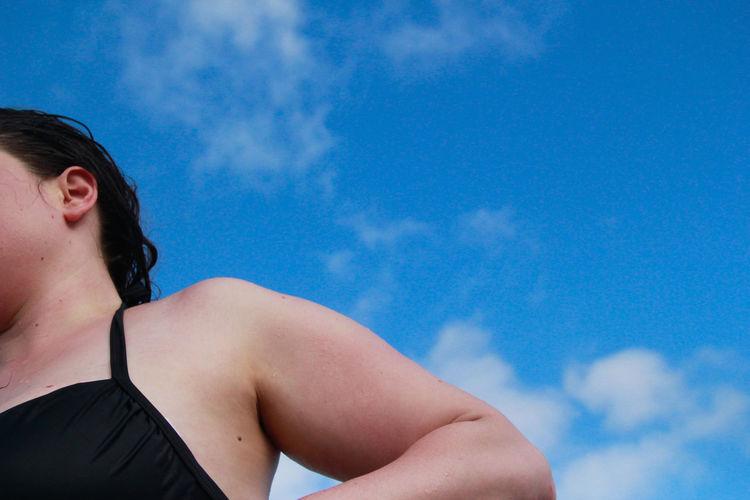 Low angle portrait of woman against blue sky