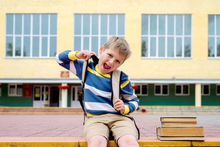 Portrait of smiling boy sitting against school building