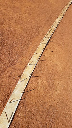 Abandoned Tennis Court White Line On Red Sand Rusted Nails Full Frame High Angle View Close-up No Filter, No Edit, Just Photography Red Sand Tennis Court Line Diagonal Line No People Outdoors