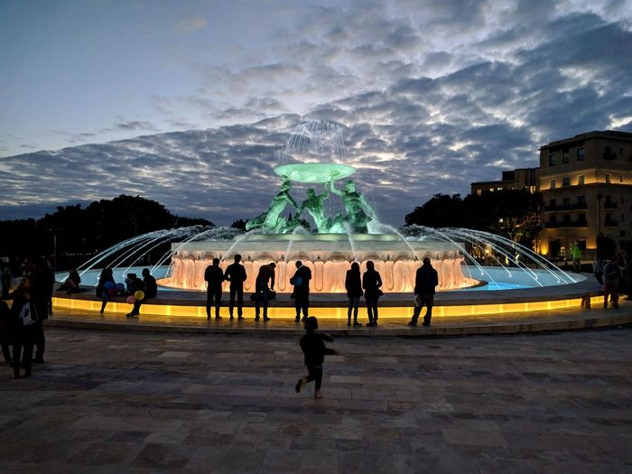 People at fountain in city against sky