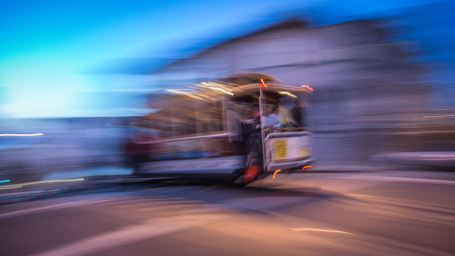 Blurred Motion Image Of Cable Car On Street At Dusk