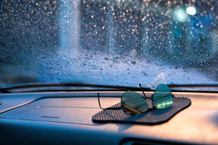 Raindrops and moisture on the car front glass with blurred sunglasses in foreground at rainy night
