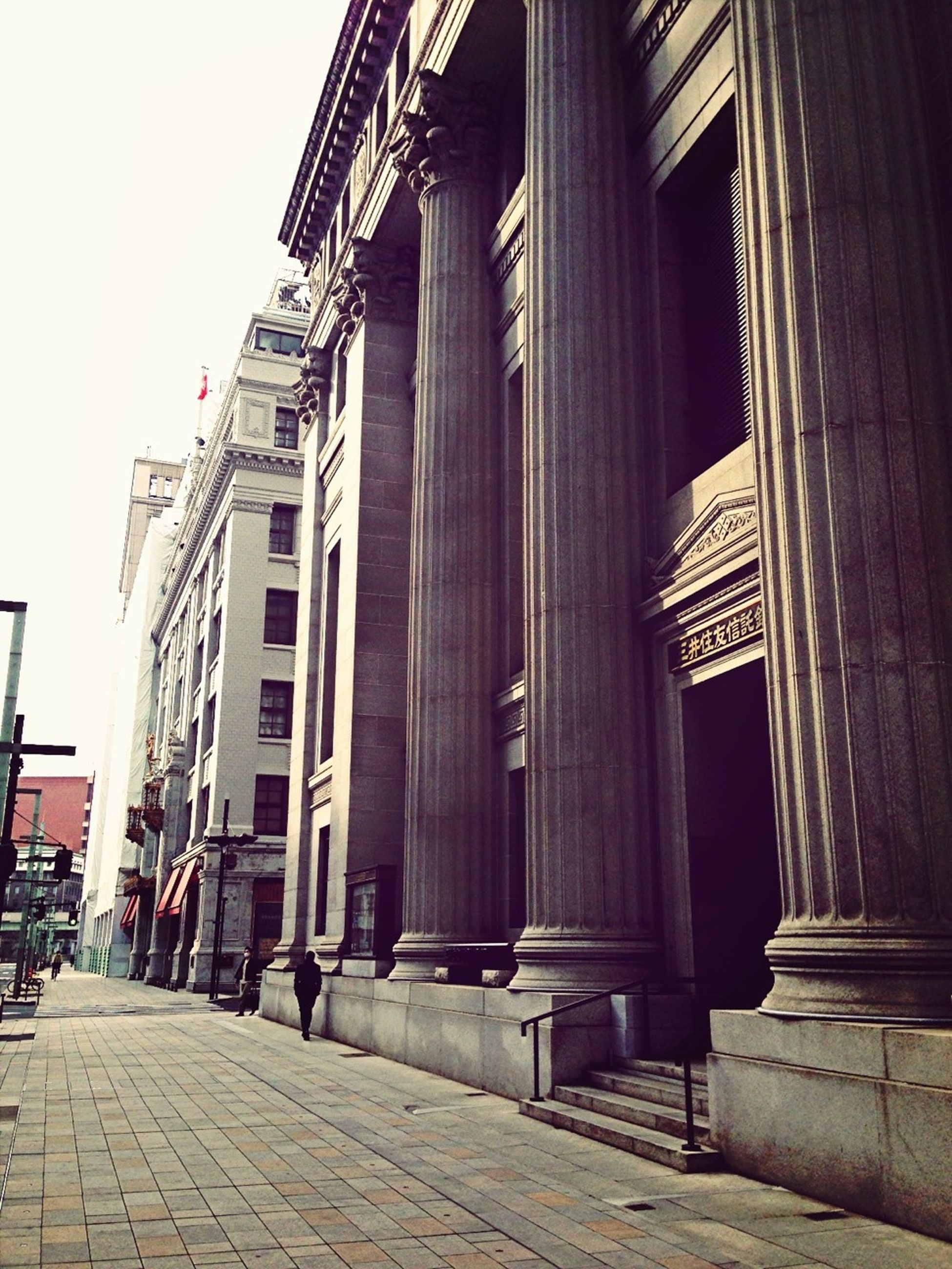 architecture, building exterior, built structure, the way forward, street, city, cobblestone, building, sky, facade, low angle view, outdoors, sidewalk, sunlight, incidental people, street light, walkway, architectural column, day, clear sky