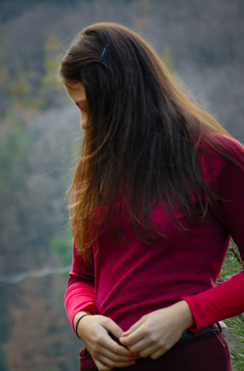 Woman in red standing outside with a blurred background