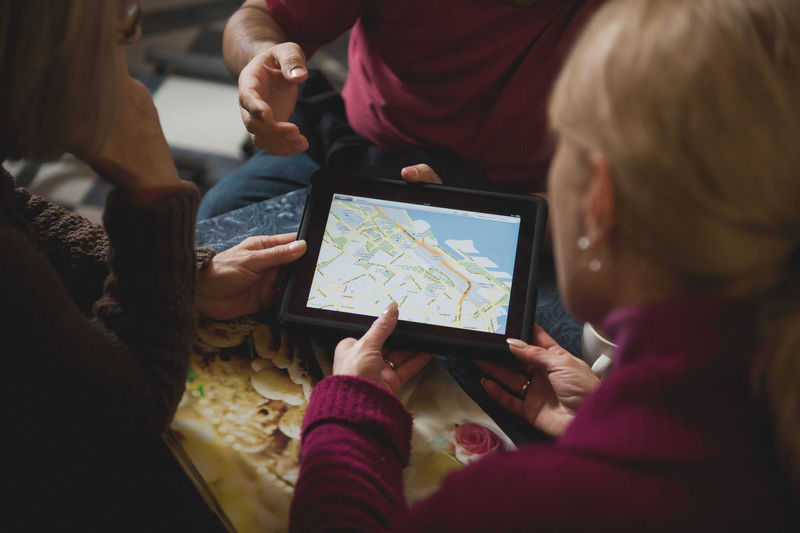 People Looking At Map On Digital Tablet