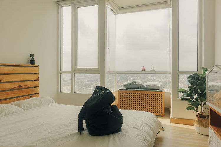 Man relaxing on bed by window at home