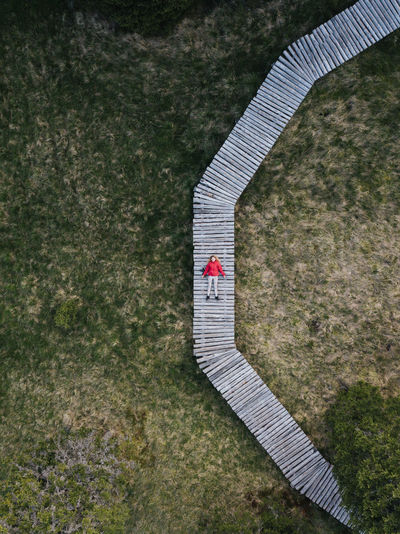 Aerial view of woman relaxing on footpath over field