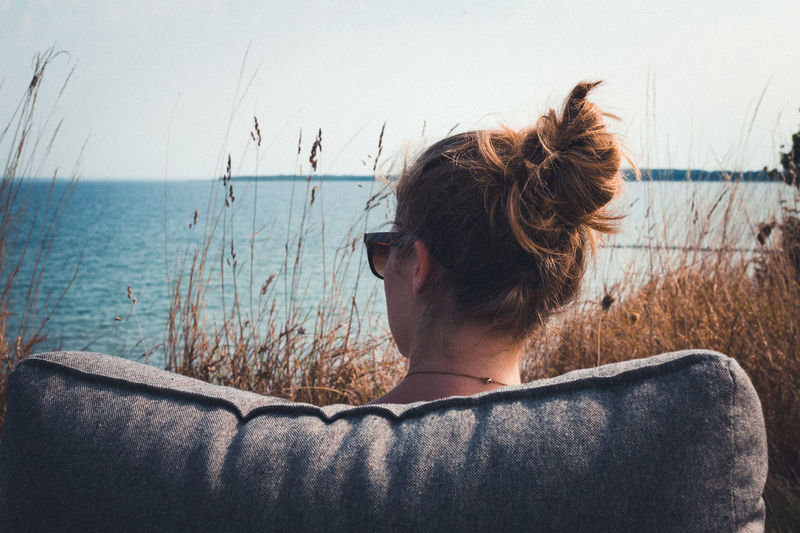 Rear view of woman sitting on couch against lake